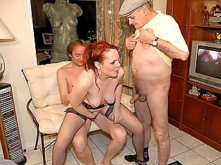 Redhead in sexy black stockings gives head and gets banged by a couple of old perverts who love young pussy
