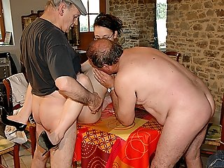 Two old grandpas team up to give cute nubile brunette in eyeglasses a fucking of her life on a table and on the floor